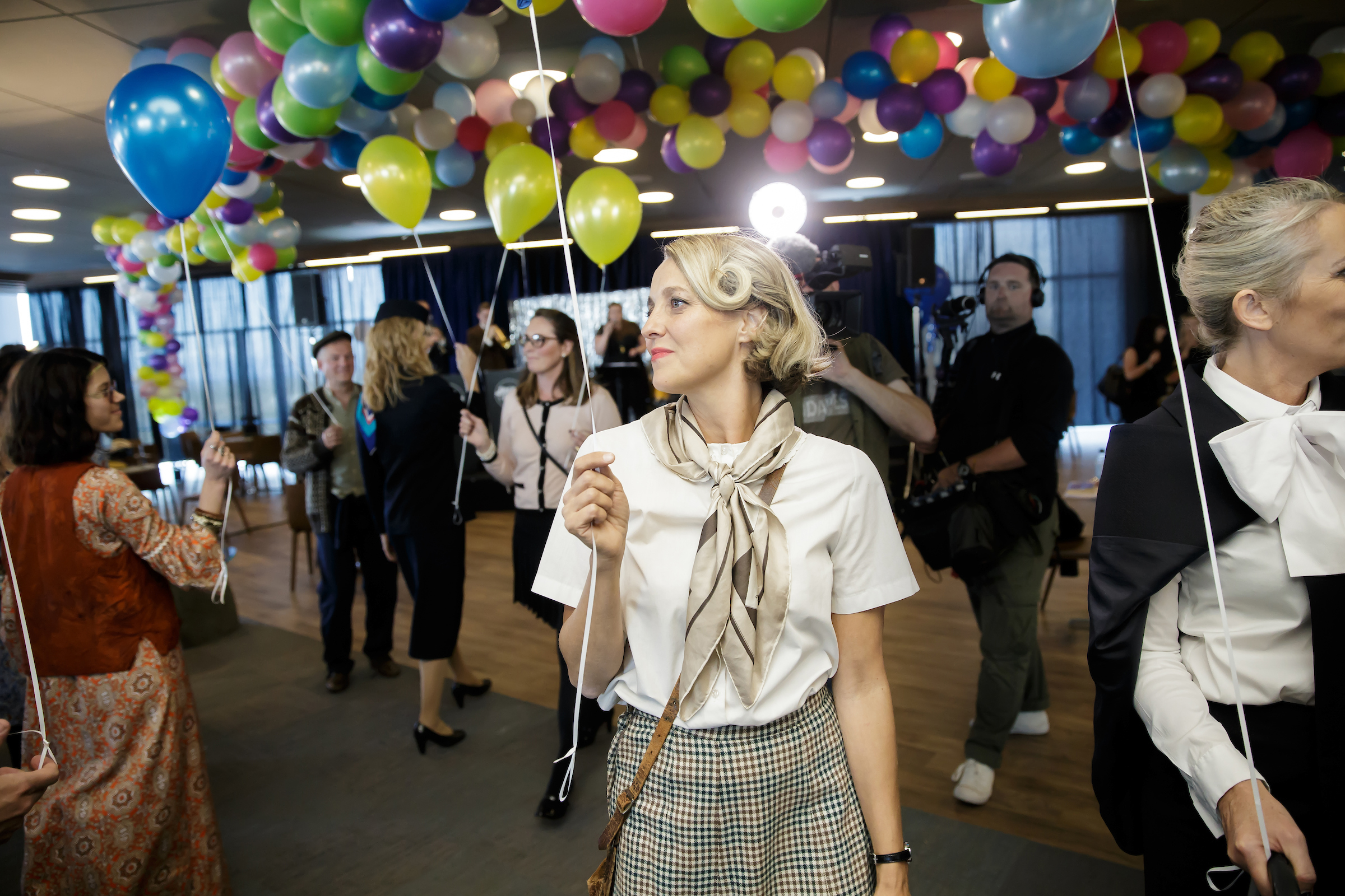 a woman stands in a somewhat crowded room holding a baloon
