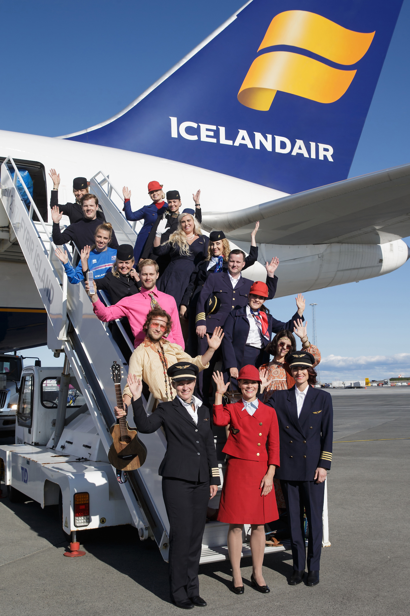 a large group of people standing on the stairs of an Icelandair aircraft, all dressed in a mix of fancy dress and Icelandair uniforms